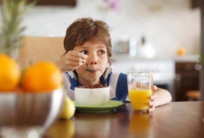 Cute-boy-drinking-orange-juice-and-eating-muesli-for-breakfast